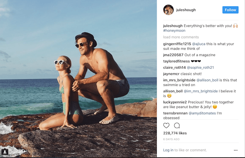 Julianne Hough and Brooks Laich crouch on a rock on a beach