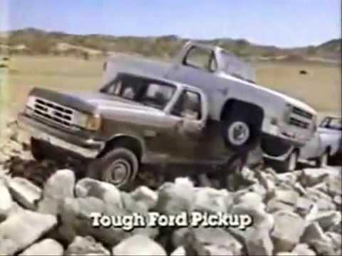 Still from a 1987 ad of a Ford F-250 hauling a Chevy truck and towing a Dodge Ram