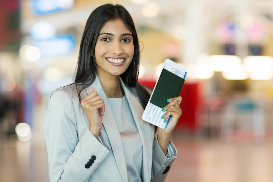 indian woman holding passport and boarding pass