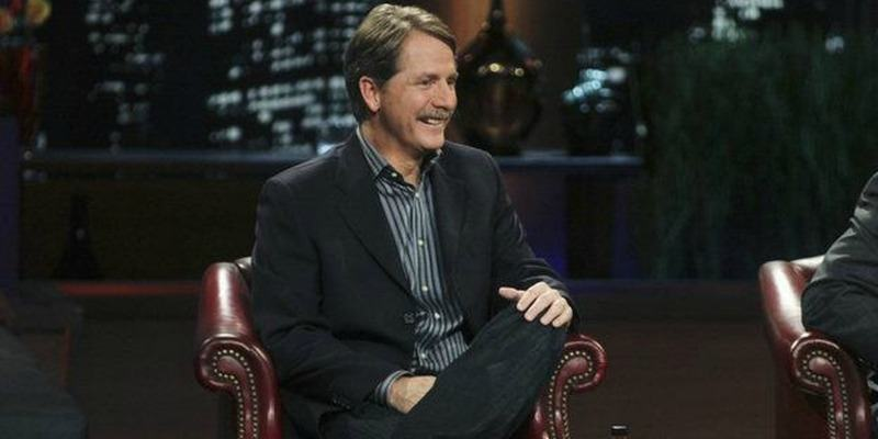 Jeff Foxworthy is sitting in a suit on Shark Tank smiling.