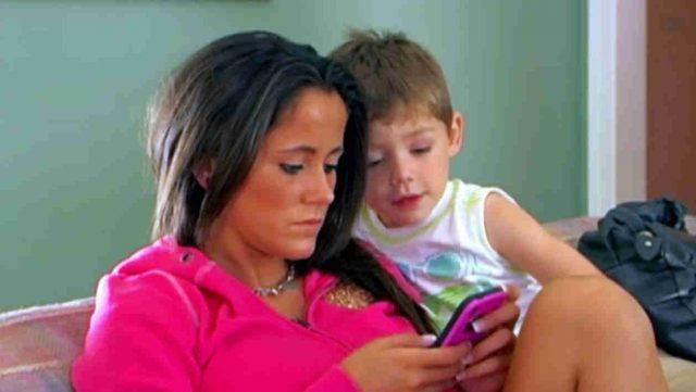 Jenelle looks at her phone as Jace looks over her shoulder.
