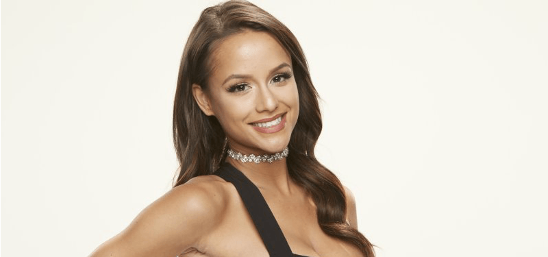 Jessica Graf is smiling and posing in a black dress on Big Brother.