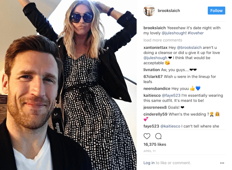 Julianne Hough stands and waves her hands above Brooks Laich