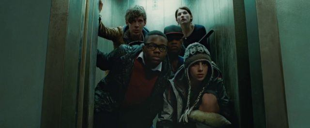 John Boyega, Jodie Whittaker and the rest of the ensemble huddle in a dimly lit elevator in a scene from 'Attack the Block'
