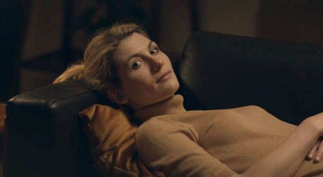 Jodie Whittaker lays on a black couch in a tan turtleneck as Ffione in the 'Black Mirror' episode, 'The Entire History of You.'