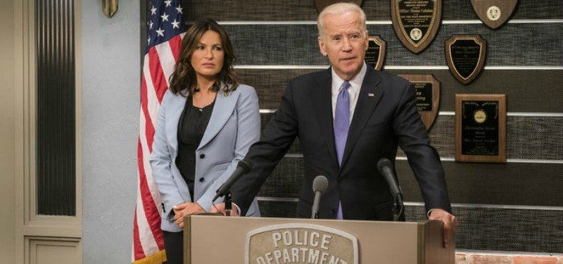 Joe Biden is speaking at a podium beside Mariska Hargitay.