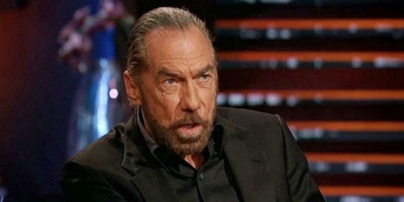 John Paul DeJoria is talking while sitting down on Shark Tank.