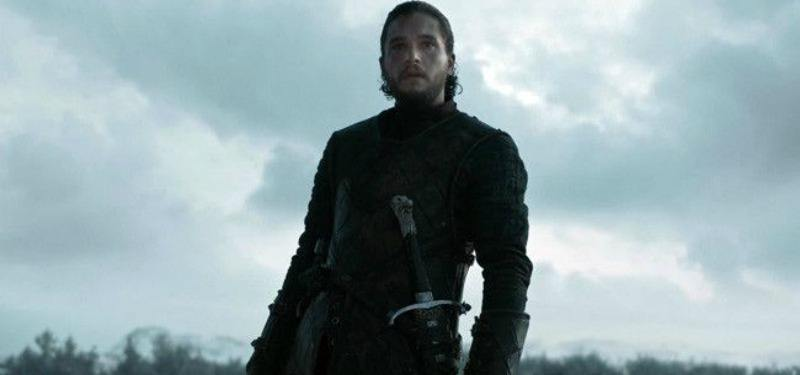 Jon Snow is on a battlefield with his sword at his waist.