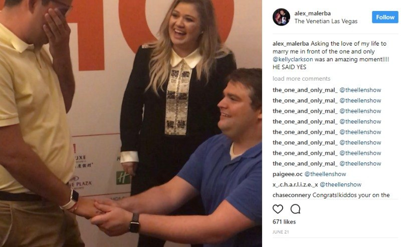 One man is on one knee as he proposes to his boyfriend as Kelly Clarkson watches.
