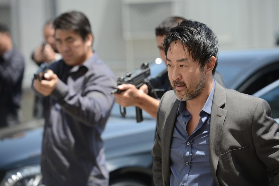 Kenneth Choi stands by men holding guns