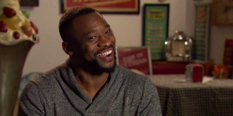 Kenny is smiling and wearing a sweater on The Bachelorette.