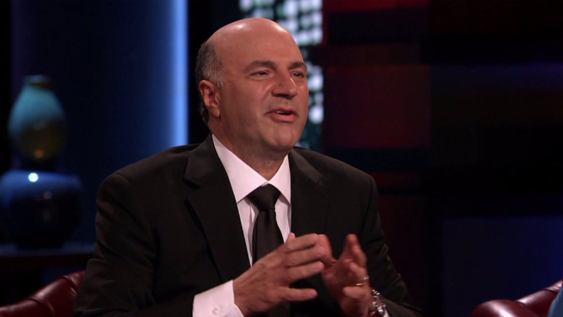 Kevin O'Leary leans forward in a chair on Shark Tank