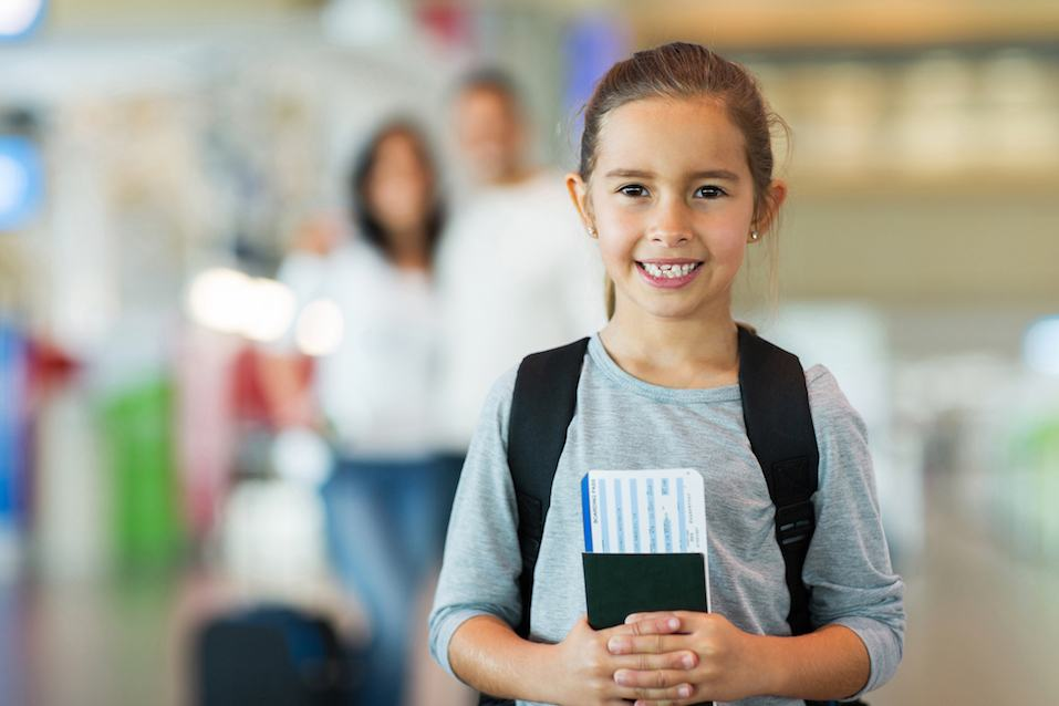 beautiful little girl holding passport and boarding pass