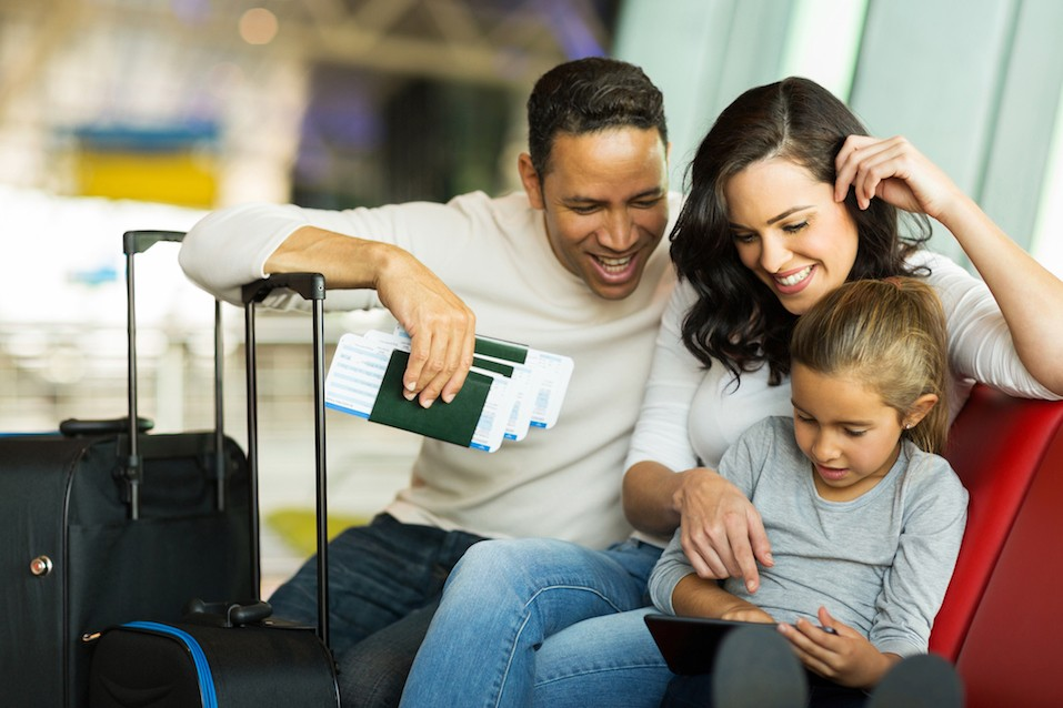 little girl using tablet pc with parents at airport