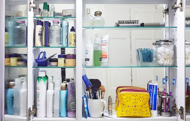 A medicine cabinet full of bottles, creams and makeup.