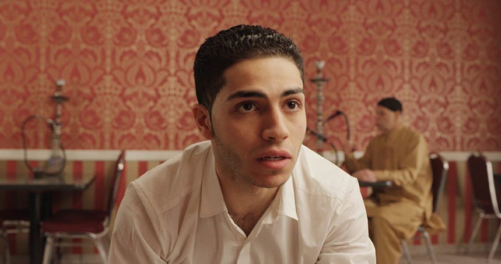 Mena Massoud as Mohammed Ali leaning forward looking scared in a hookah bar.