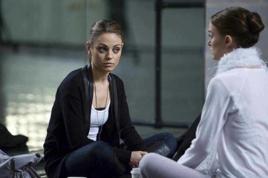 Mila Kunis sits cross-legged on the floor and looks at Natalie Portman in Black Swan