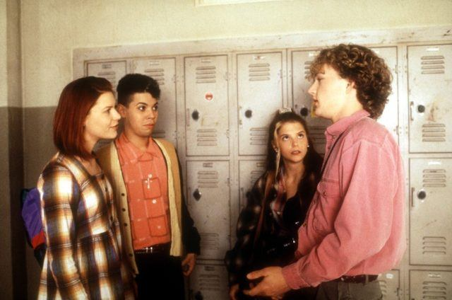 Angela, Rickie, Rayanne, and Brian stand in front of lockers talking to each other.