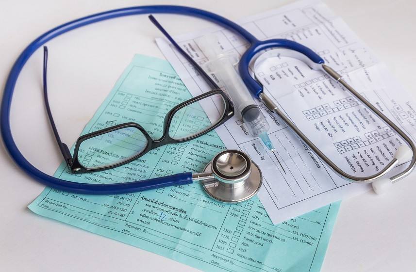 a doctor's glasses, stethoscope, and needle