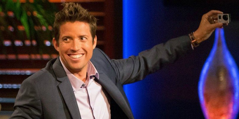 Nick Woodman is smiling and taking a picture of himself with a small camera on Shark Tank.