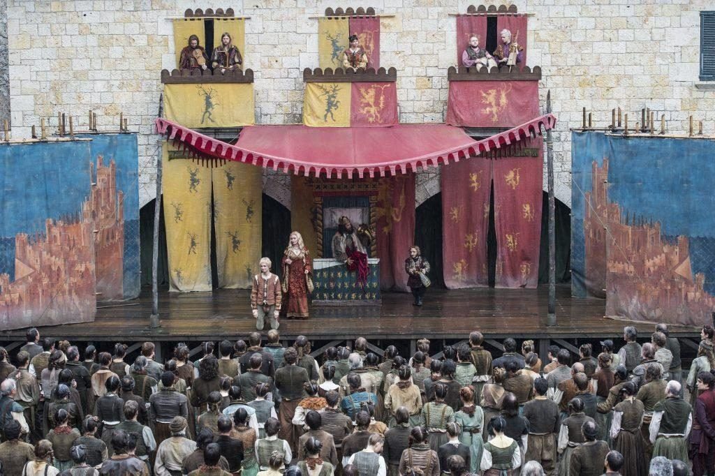 A crowd of people watching a play with actors on stage and musicians in the balconies