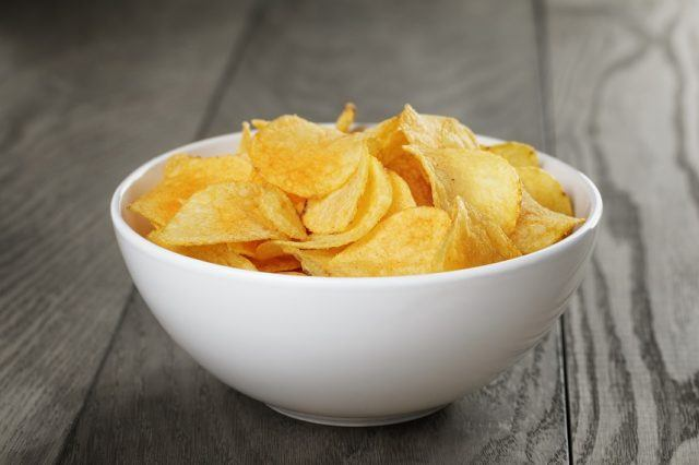 Potato chips in white bowl on a wooden table.