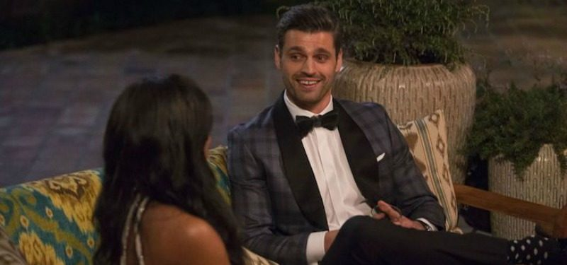 Peter Kraus sits on a couch in a suit and talks to Rachel Lindsay on The Bachelorette.