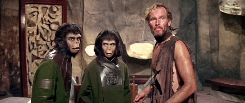 Two apes and a man standing together