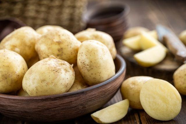 Potatoes in a wooden bowl on a table.