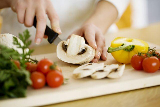 Female chopping food ingredients on a board.