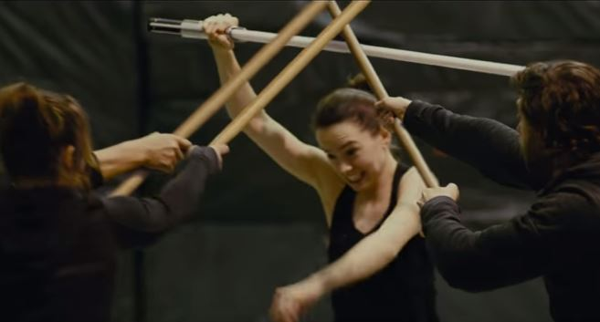 Daisy Ridley trains against three other fighters with a faux lightsaber