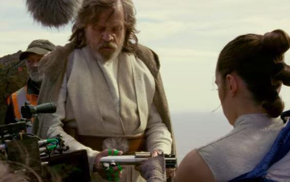 Rey hands Luke his old lightsaber.