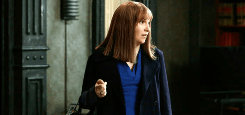 Lena Dunham is in a longer brown wig in an office.