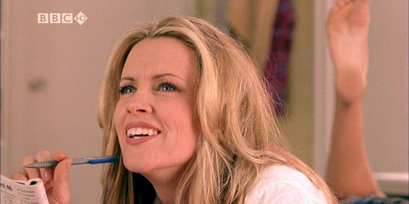 Jenny McCarthy is holding a pen and magazine while sitting on a bed.
