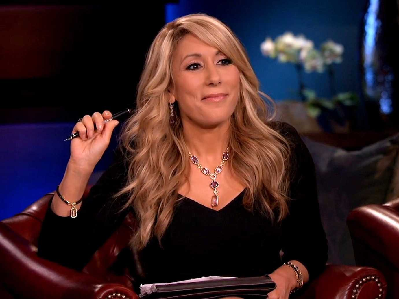 Lori Greiner smiles and holds up a pen while sitting in a chair on Shark Tank