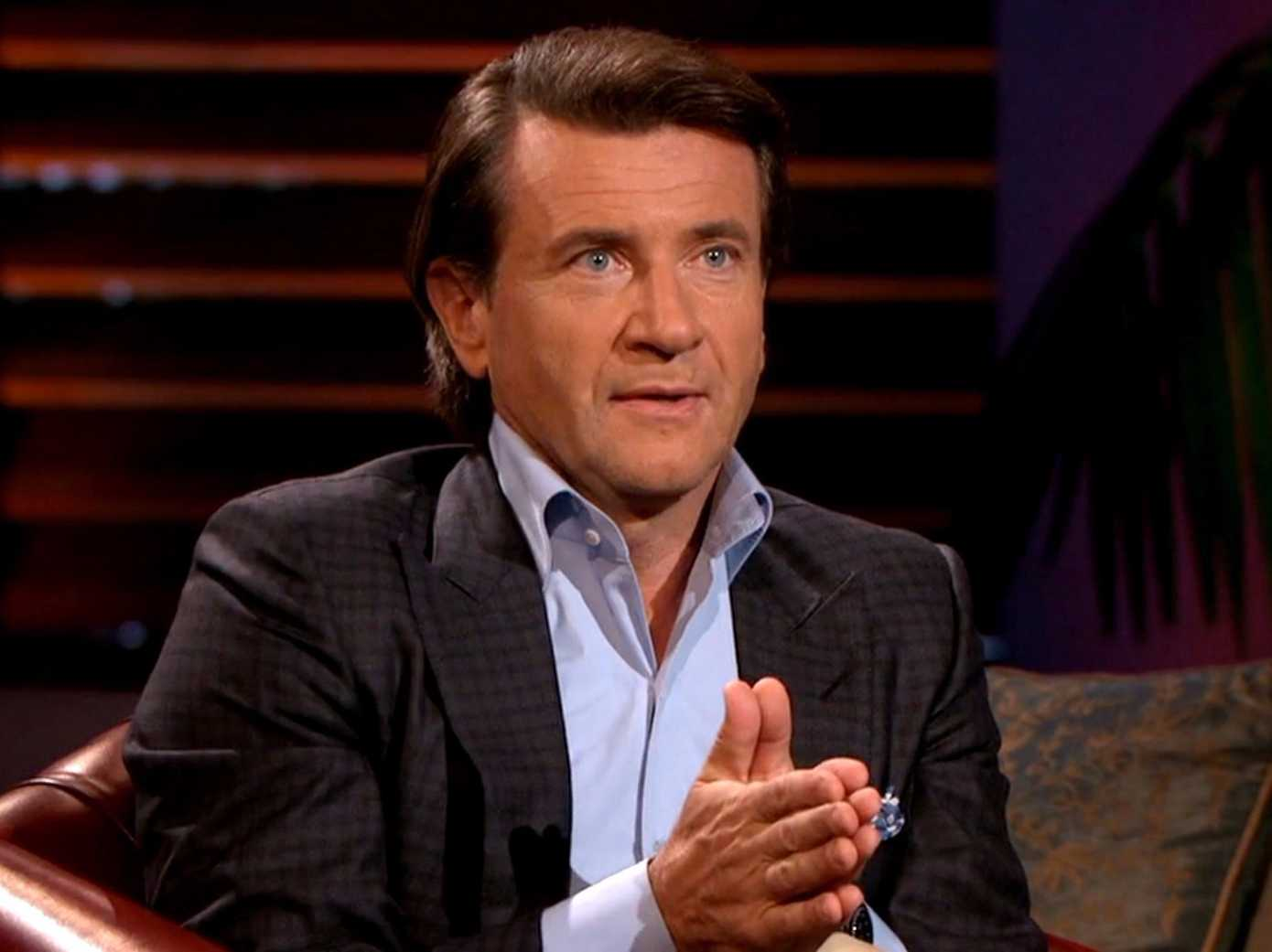 Robert Herjavec holds his hands together and learns forward in his chair on Shark Tank