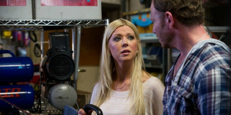 Tara Reid is talking to a man while holding a saw in Sharknado.