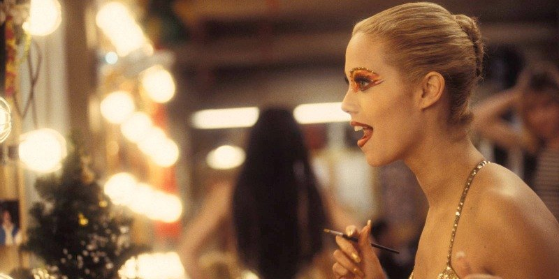 Elizabeth Berkley in Showgirls is putting on makeup and looking in a mirror.