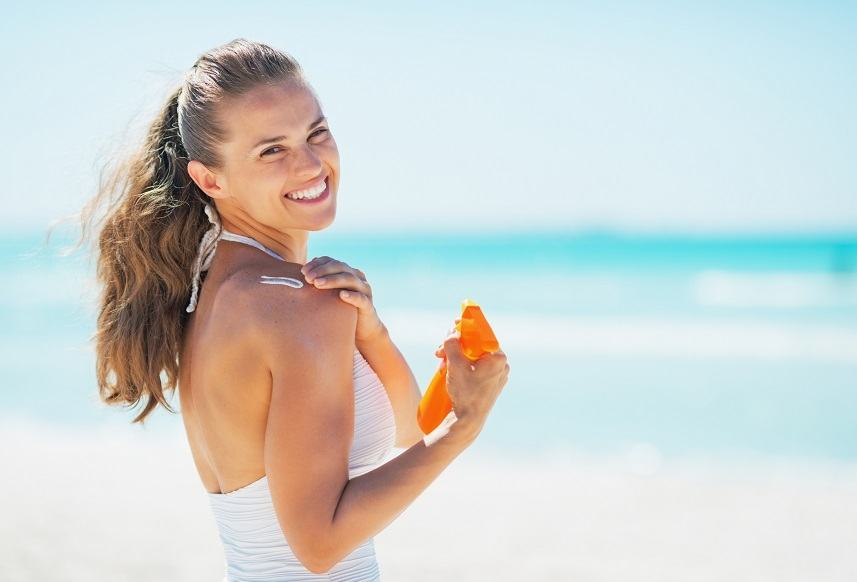 woman on beach applying sun block