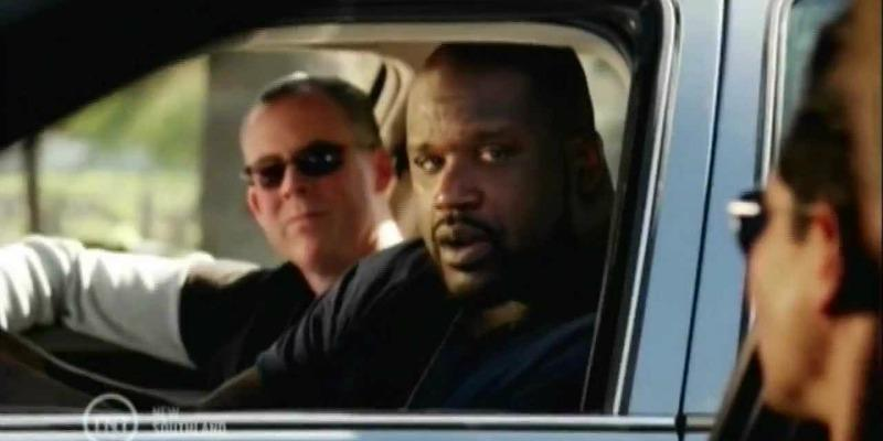 Shaq is in a cop car looking out the window in Southlands.