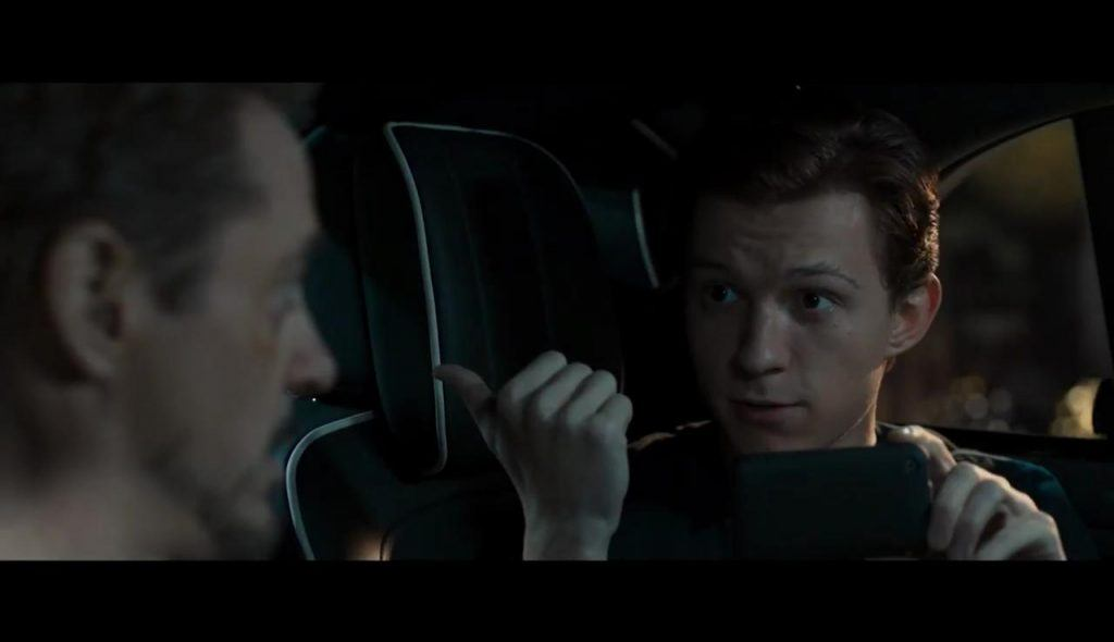 Tony Stark talking to Peter Parker who is holding his phone in the back of a limo