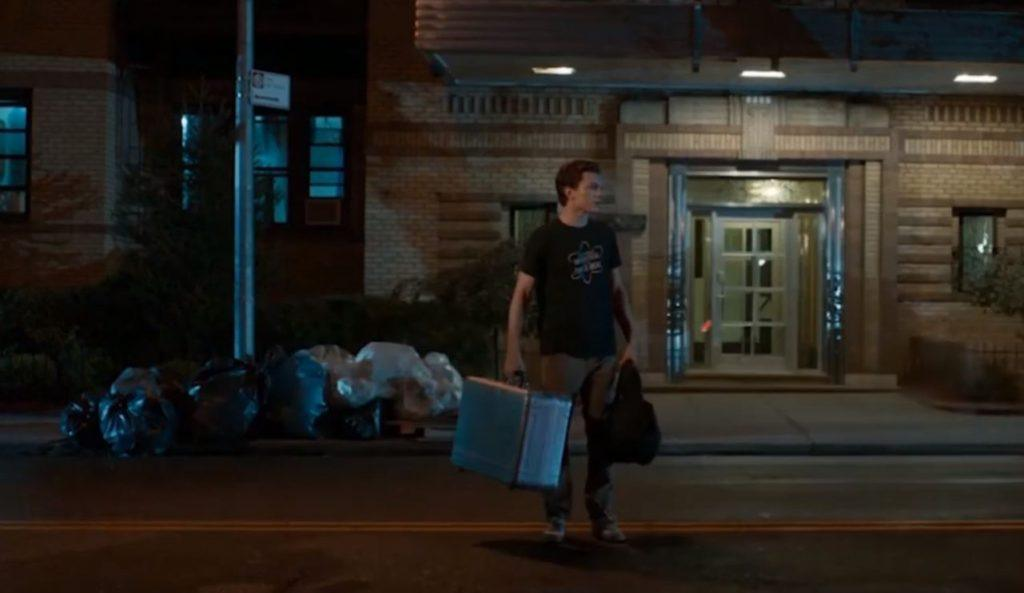 Tom Holland as Peter Parker holding a suitcase outside of a building