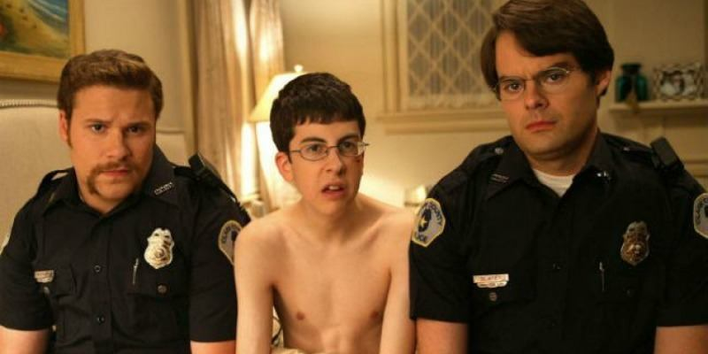 McLovin is sitting in just a towel around his waist between two police officers.
