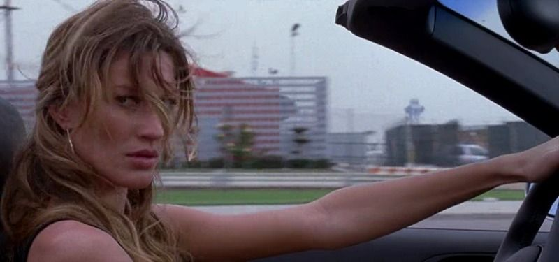 Gisele Bündchen is looking to the side as she drives a convertible.