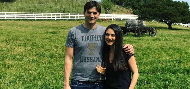 Ashton Kutcher has his arm around Mila Kunis as they stand in a field.