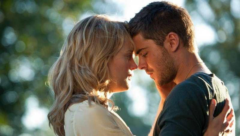 Zac Efron and Taylor Schilling are leaning their heads against each other as they're about to kiss.