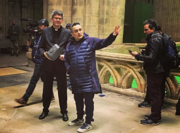 Two men stand on the set of Avengers : Infinity War holding Thor's hammer