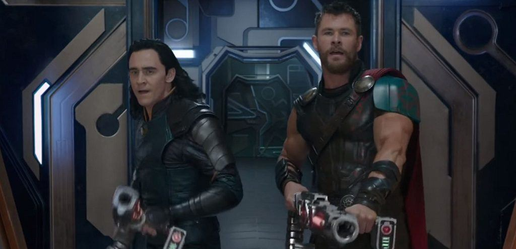 Loki and Thor stand next to each other and aim laser guns in Thor: Ragnarok