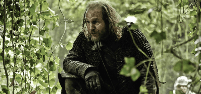 Thoros of Myr is on one knee in the woods.