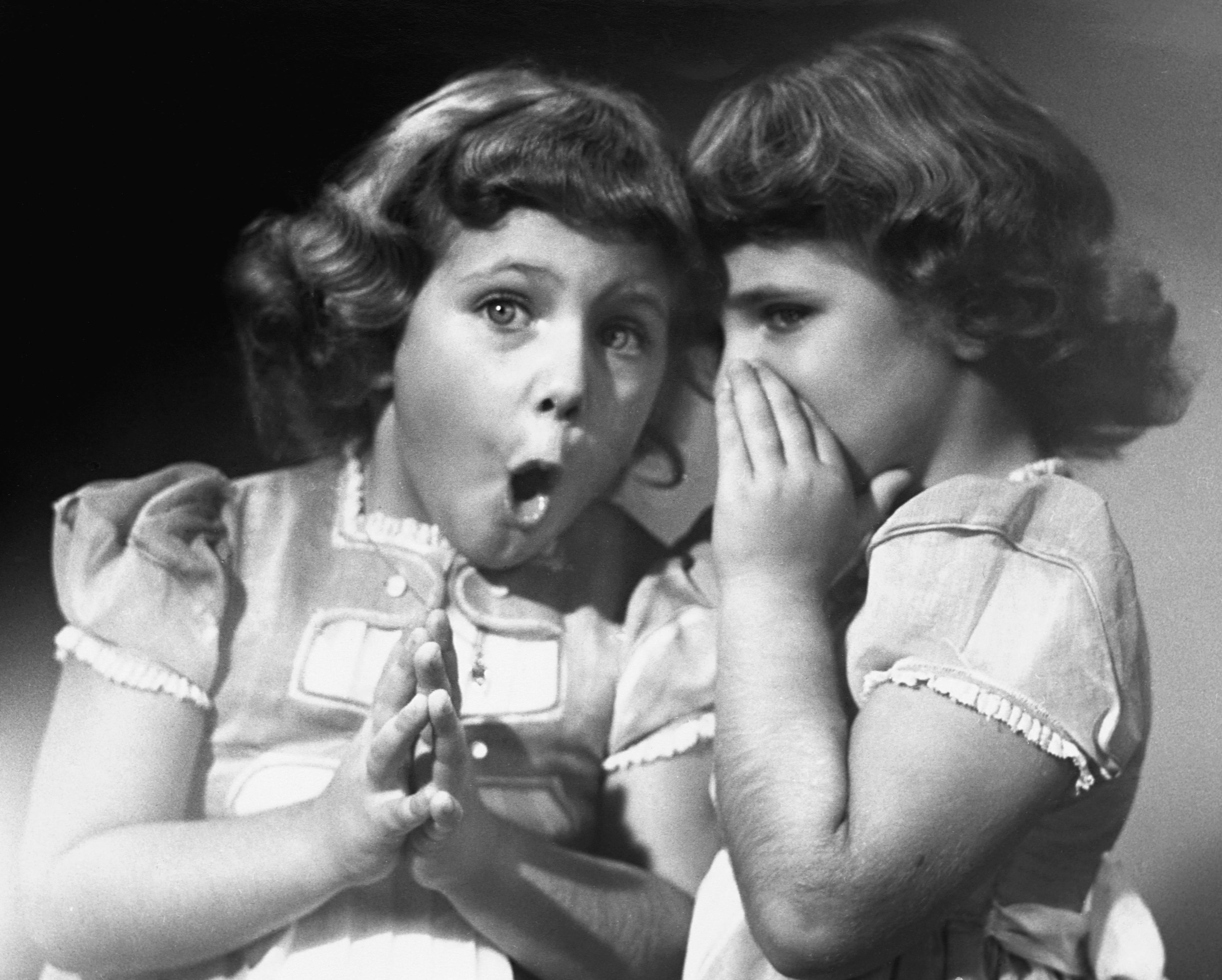 Twin sisters sharing secrets